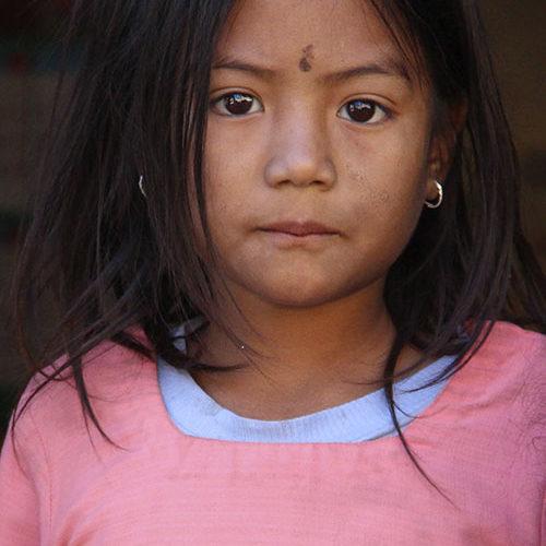 """Titel: Bahini would rather go to school (1/10) Fotograf: Anna Idegren Rydh  Många barn, främst flickor, arbetar som hemhjälp. Denna grupp är kanske en av de mest utsatta, eftersom ingen ser vad som försiggår inom husets väggar.   Många av dem har långa hårda arbetsdagar i stället för att gå till skolan.  Bahini betyder lillasyster på nepalesiska.  Den här flickan höll på att sopa golvet i huset när vi stannade till. Vi lockade ut henne med hjälp av mitt mobilskal. Det hade en 3D bild av en påfågel som motiv.  Fotot visades på utställningen """"Himalaya in Sight"""" i Gamla stan 2013.  Fotot har en begränsad upplaga."""